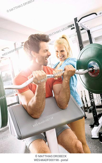 Young couple training with EZ curl bar at gym