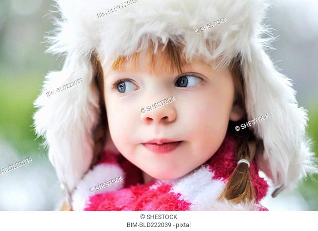 Caucasian girl wearing fuzzy hat outdoors