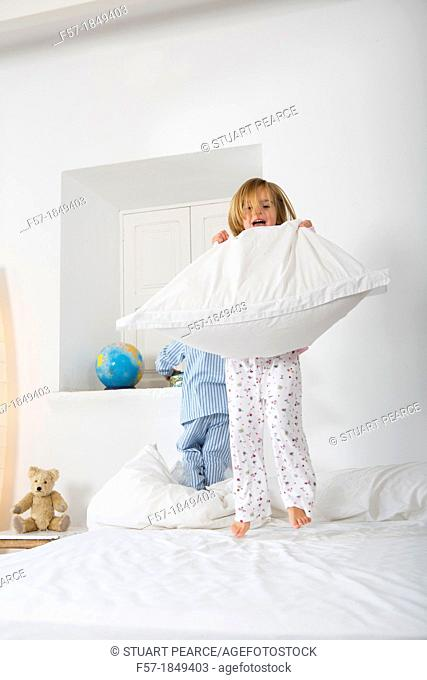 Four year old girl jumping on the bed