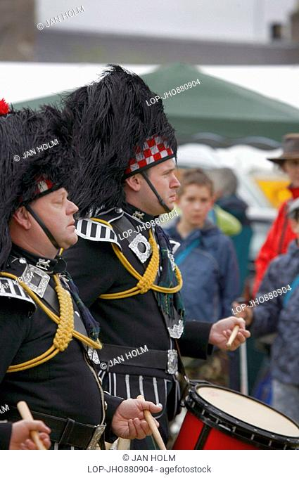 Scotland, Aberdeenshire, Strathdon, Drummers from The Ballater and District Pipe Band performing at the Lonach Gathering and Highland Games, billed as