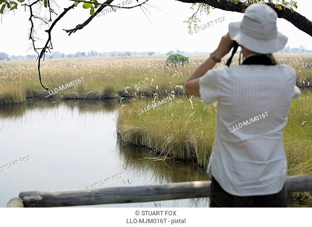 View of woman on safari looking at the Okavango River and floodplain through binoculars, Okavango Delta, Botswana