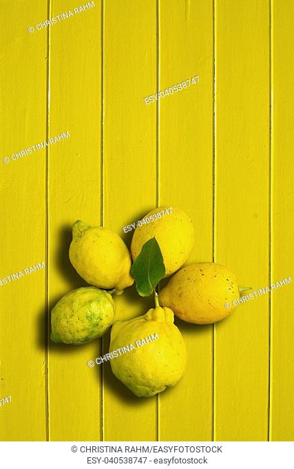 Five lemons on yellow painted wood background vertical copy space