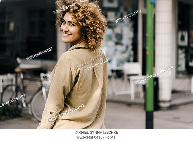 Woman in the city, walking away, smiling
