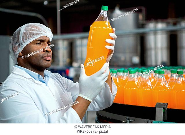 Male worker checking products in juice factory