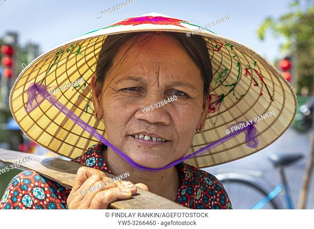"""Portrait of an elderly Vietnamese woman wearing a traditional sampan hat also known as a """"""""rice hat"""""""". Hoi An, Quang Nam provence, Vietnam, Asia"""
