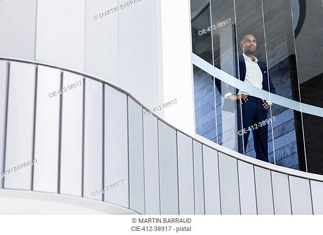 Confident CEO businessman standing in modern office window