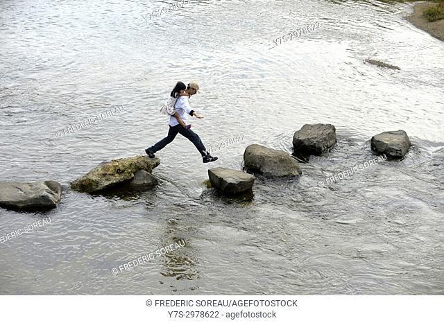 Japanese man with a little girl jumping along Miyagawa river in Takayama, Japan, Asia