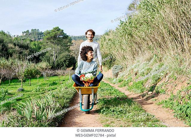 Woman sitting in wheelbarrow, holding fresh vegetables, man pushing her