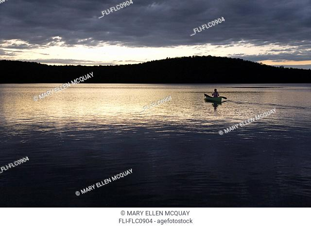 Woman canoeing solo at sunset, Algonquin Park, Ontario