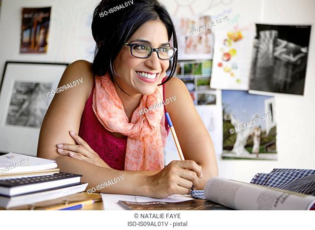 Mid adult woman at desk wearing glasses