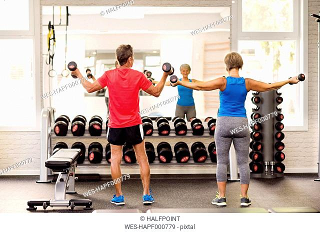 Senior man and mature woman working out in fitness gym