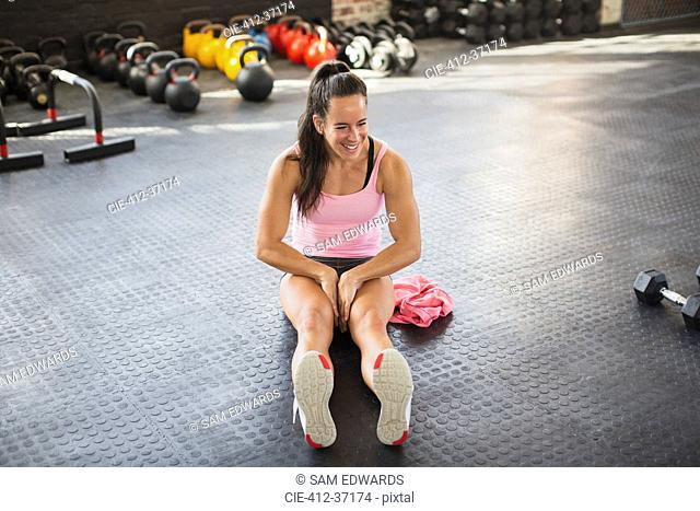 Muscular young woman stretching legs in gym