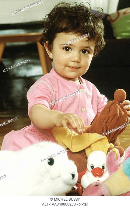 Little girl sitting with toys, portrait