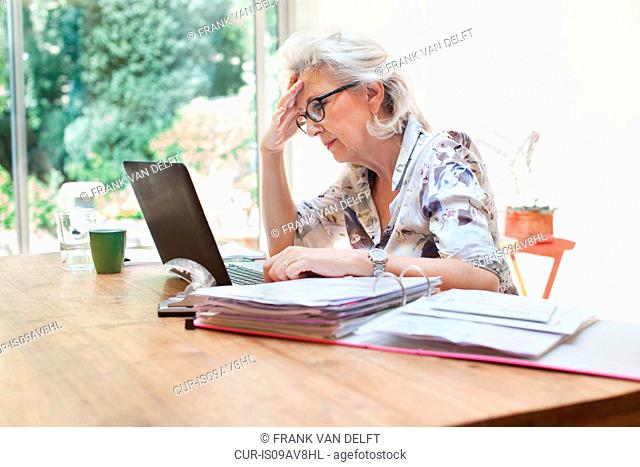 Senior woman sitting at table, using laptop, worried expression
