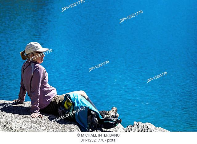 Female hiker sitting on rock face overlooking alpine lake; Vermillion Crossing, British Columbia, Canada