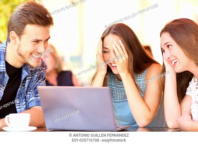 Happy friends giving a laptop gift to a surprised girl in a coffee shop