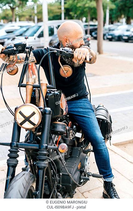 Mature male hipster astride motorcycle, looking over his shoulder