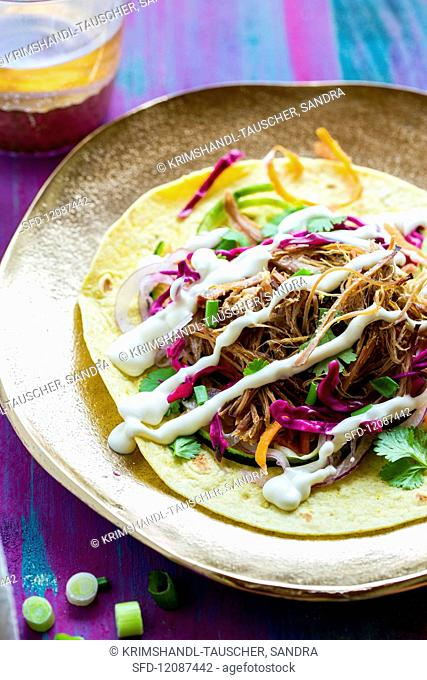 Tortilla with pulled pork, vegetables and sour cream