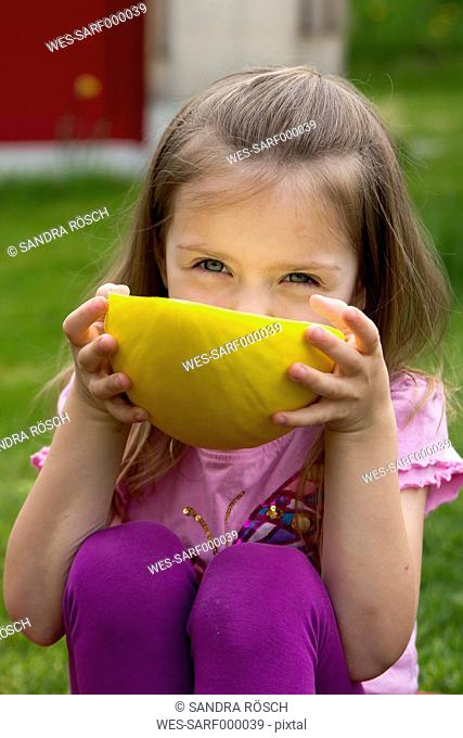 Germany, Bavaria, Girl eating honeydew melon, close up