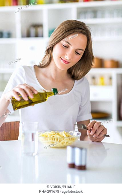 Woman pouring olive oil on pasta