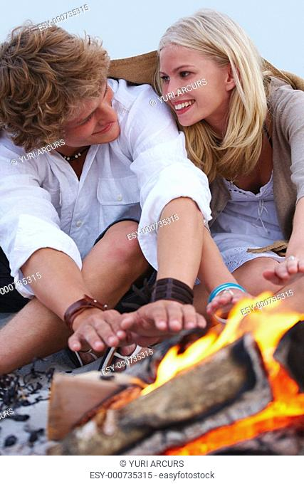 Happy young couple warming hands on fire at the beach