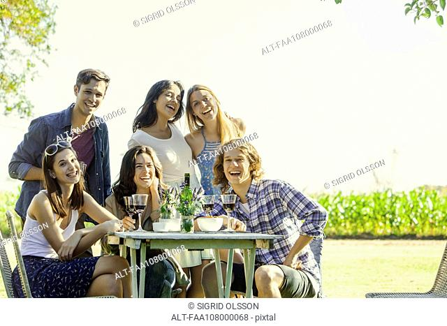 Friends posing for photo during outdoor meal together