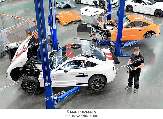 Engineer repairing racing cars in racing car factory