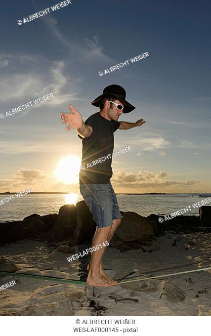France, Bretagne, Landeda, Man balancing on slackline on beach