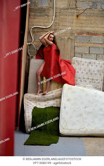 fashion model woman shrouded in red tarpaulin on mattresses in backyard