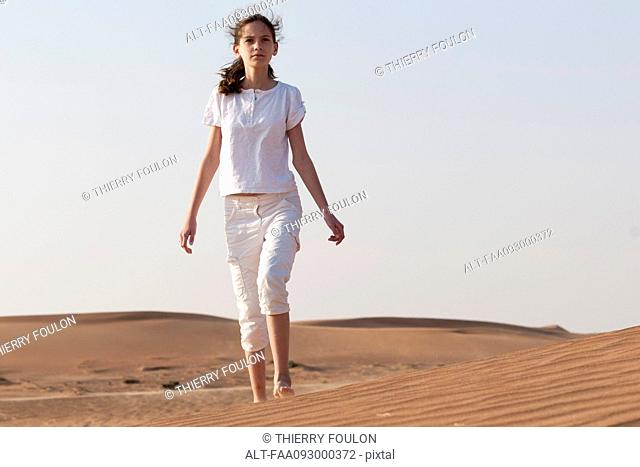 Girl with forlorn expression alone in desert
