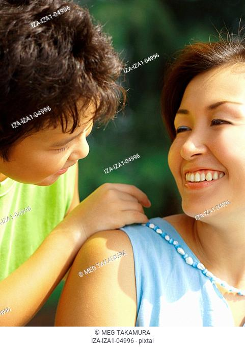 Close-up of a boy putting a necklace around his mother's neck and smiling