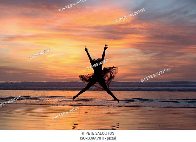 Young female dancer wearing chiffon dress, dancing, in mid air, on beach at sunset, San Diego, California, USA