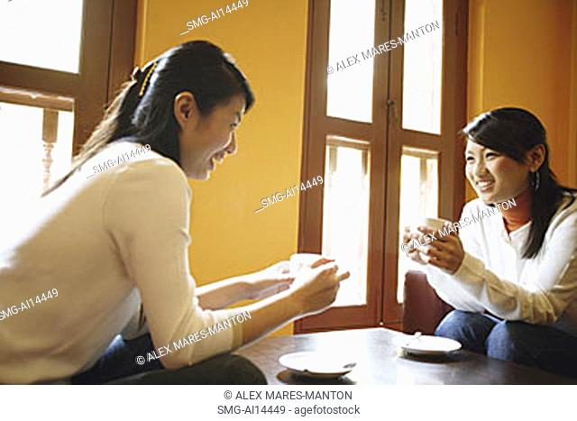 Two young women, holding cups of coffee, talking