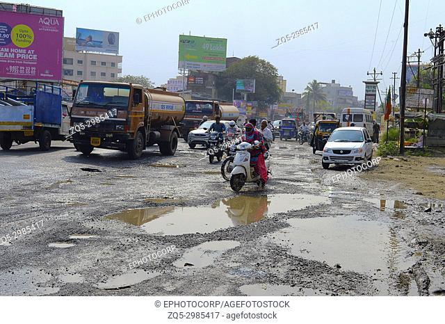 People driving on damaged road with potholes, Pune, Maharashtra
