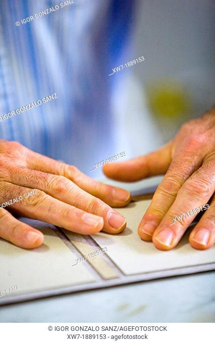 Craftsman bookbinder working in manual binding of a book or craft book