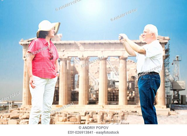 Senior Man Taking Photograph Of His Wife Against Parthenon Temple