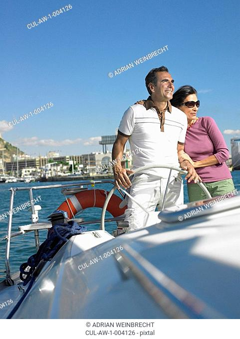 Mature couple at wheel of yacht, smiling