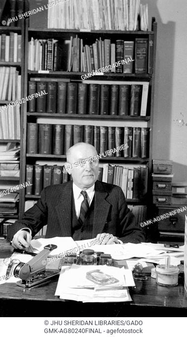 Candid portrait of Manager of The Johns Hopkins Press Christian William Dittus sitting at his desk surrounded by papers and books, 1940