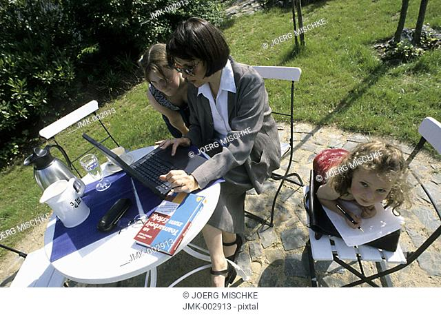 A woman, businesswoman, mother, 40-45 45-50 years old, sitting at the table in the summerly garden, working at the laptop and a two girls, 1-5 5-10 years old