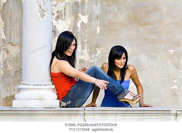 Two young female friends are looking at someone