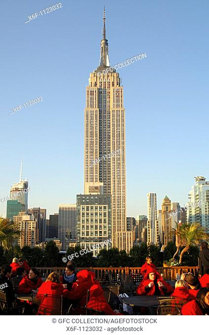 Roof-top terrace bar with view at the State Empire Building overtops all other high-rise buildings in Manhattan, New York, USA