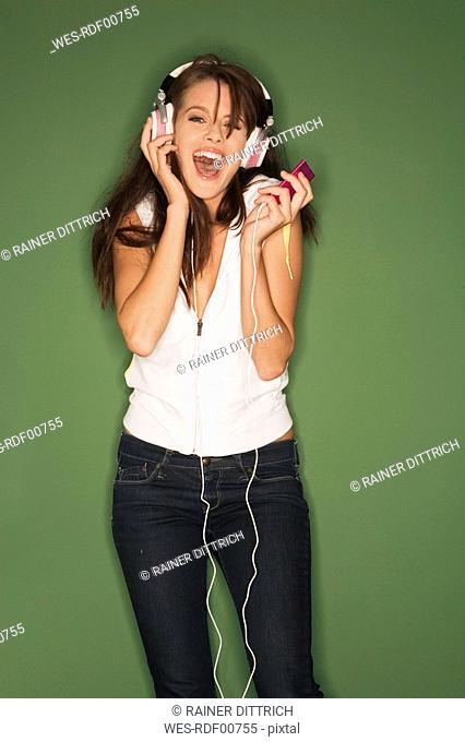 Young woman listening to music from MP3 player