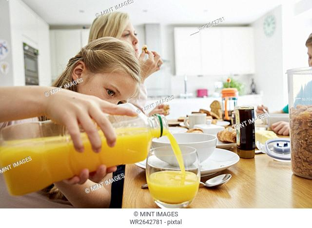 A family seated at breakfast, a girl pouring a glass of orange juice