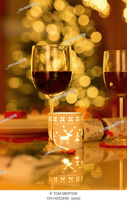Red wine and Christmas candle on dining table