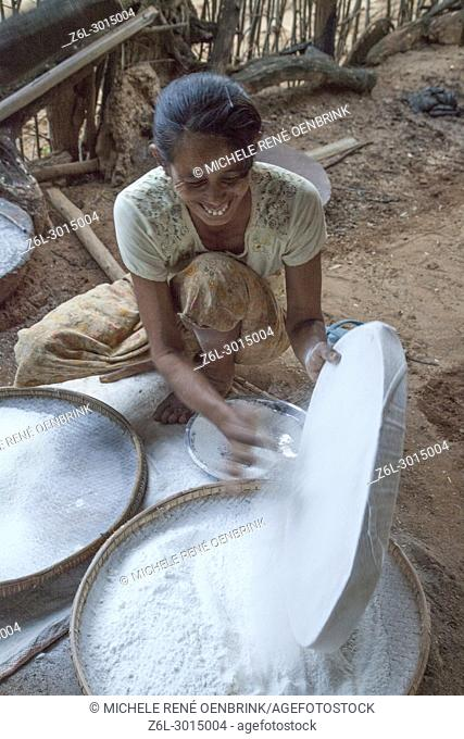 Local Burmese woman in small town outside Bagan Myanmar making flour