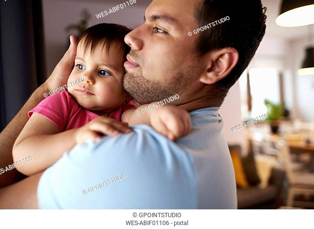 Affectionate father hugging his baby daughter at home