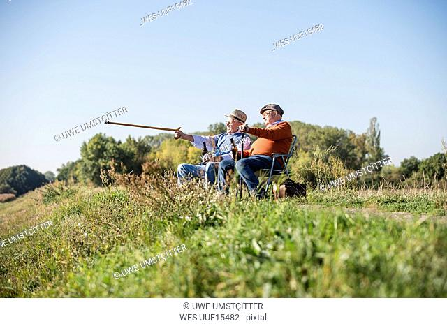 Two old friends sitting in the fields, drinking beer, pointing with walking stick