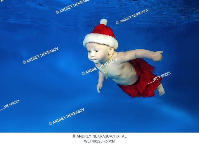 small girl in Santa's red cap swimming underwater in the pool