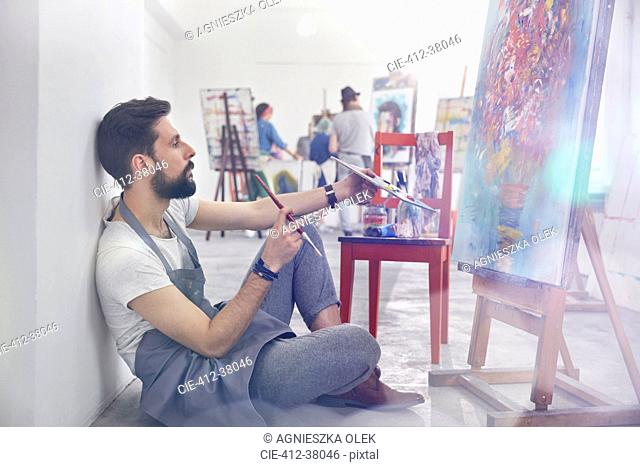 Male painter painting, examining painting in art class studio