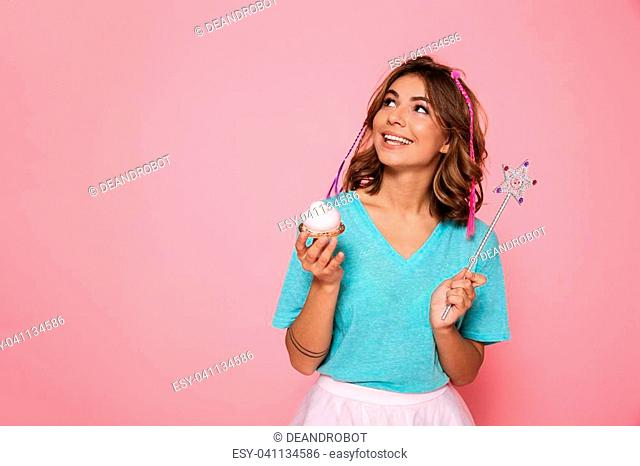 Charming brunette girl with magic wand holding cupkake looking aside, isolated on pink background